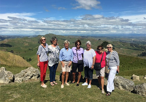 The travel group posing for a picture overlooking an expanse of greenery