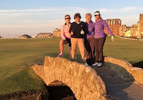 Mary and travel group standing on a bridge on a golf course